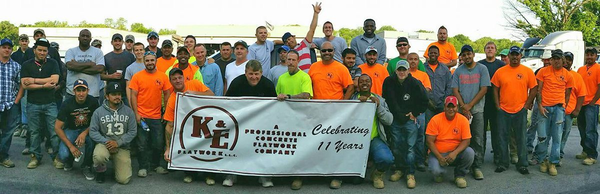 Ke flatwork company photo while holding banner