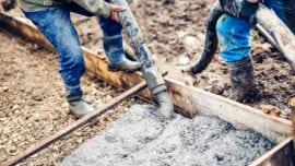 workers handling massive cement pump tube