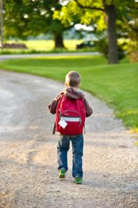 boy walking in a school sidewalk