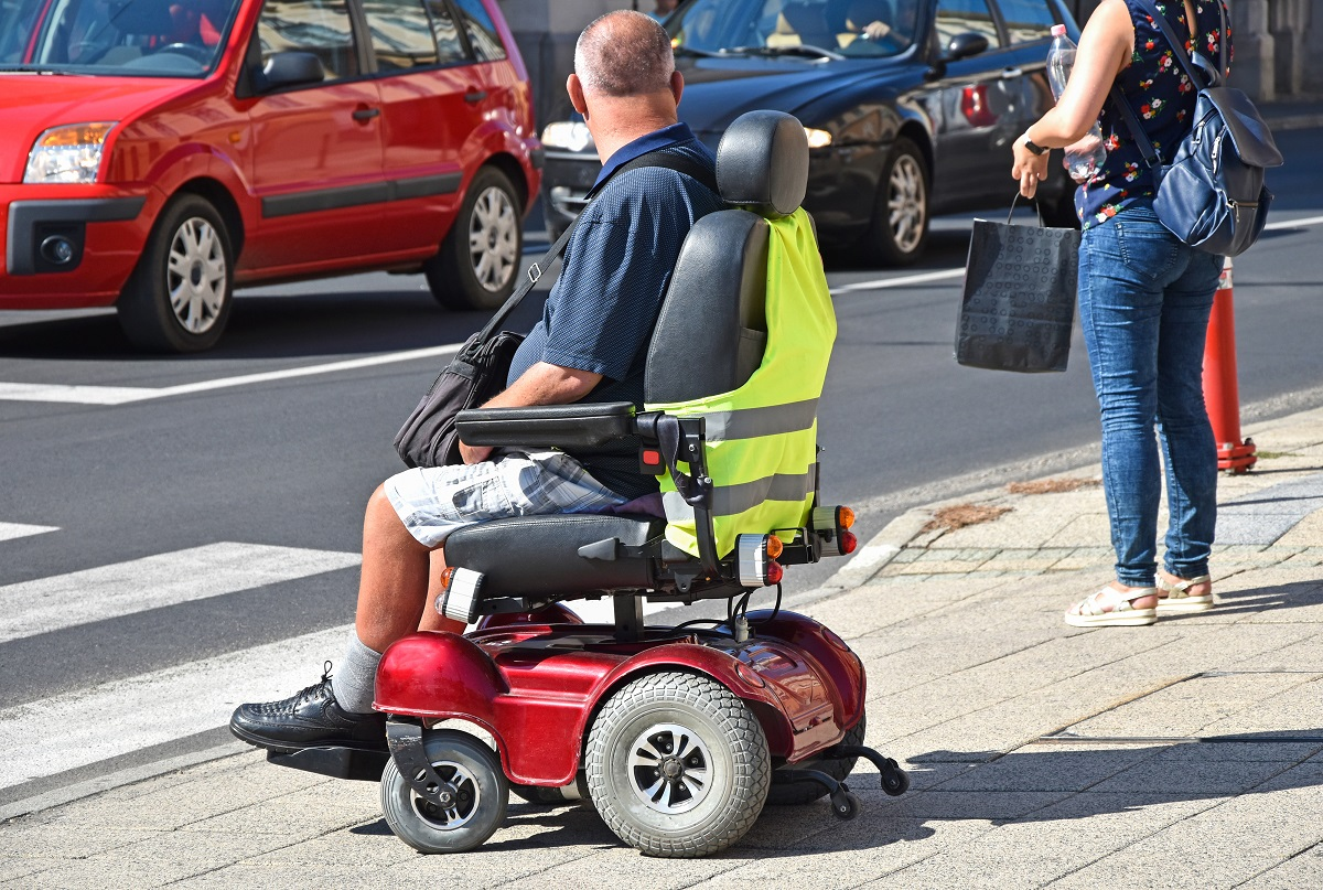 PWD On A Electric Wheelchair At The Sidewalk